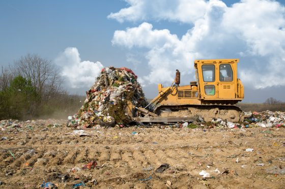 The old bulldozer moving garbage in a landfill